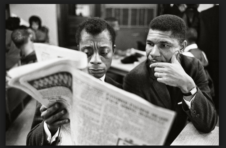 James Baldwin with good friend Medgar Evers reading the news. Photo Courtesy of Steve Schapiro via the New York Times.